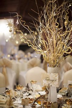Gold twig centrepieces with fairy lights and hanging decorations on a mirrored base