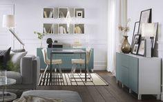 Salón con una zona para comer compuesta por una mesa en cromado/vidrio blanco y unas sillas en cromado/piel blanca. Armarios blancos con puertas y frentes de cajón en gris-turquesa.