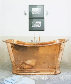 The impressive copper tub at the heart of designer Kelvin Browne's bathroom is decidedly old-fashioned and seems to glow against the contrasting spareness of the contemporary concrete floor. | Photographer: Virginia Macdonald