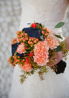Peach, brown, and orange bouquet featuring carnations and hypericum.