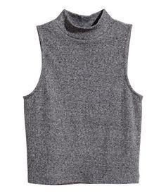 Camiseta corta en punto de canalé, sin mangas y con cuello alto.