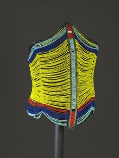 Africa | Dinka man's Corset. Dinka men regularly wear beaded corsets, partly as indicators of their age group and position. The yellow beads in this corset suggest that it may have been designed for a man over the age of thirty. The glass beads and wire used in making such corsets are imported products, making the outfits considerable markers of status and prestige. Sudan, 20th Century.