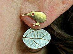 """Vergold. Kiwi & echtes Blatt Doppel Ohrringe Handvergoldeter kleiner Kiwivogel und darunter ein echtes Blatt.  Besonderer Clou: das Blatt ist der Rückstecker des Kiwi. Es wird also hinten aufgesteckt und damit der Kiwi geschlossen. Durch Zusammendrücken bzw. Auseinanderziehen des Ohrrings könnt ihr den """"Sitz"""" des Blattes nach Geschmack und Ohrform anpassen. Die beiden Fotos am Ohr zeigen dies: einmal sitzt des Blatt enger und knapp hinter dem Ohrläppchen."""