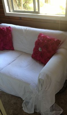 DIY Couch slip cover: white sheets, safety pinned in place. Gathered corners and tied with bows made from tulle.