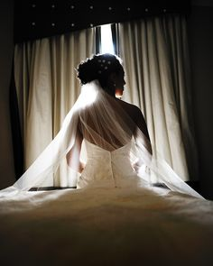 partly silhouetted shot in window light - back of brides dress and full length veil - side profile of brides face - photo by New York City based wedding photographer Ryan Brenizer