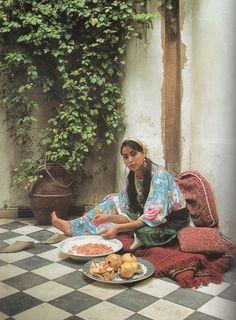 Moroccan women preparing pomegranate.