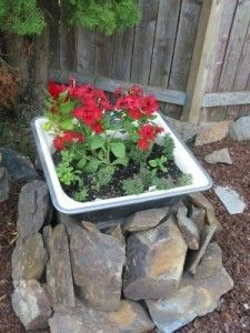This neat little repurposed kitchen sink project has been mounted on rocks as a feature planter.  Instantly make it colorful with our flowers from Old Time Pottery Garden Centers!  http://www.oldtimepottery.com/