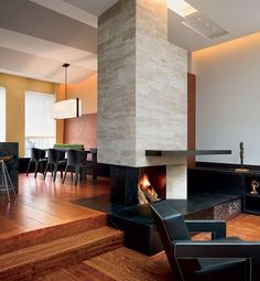 To create his Manhattan residence, violinist Joshua Bell worked with architect Charles Rose, who—at Bell's request—put a limestone-tiled fireplace between the living and dining areas. The patinated-steel mantel cantilevers out on one end to double as a bar.