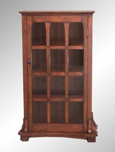 """Solid oak reproduction 12-grillwork divided section glass door bookcase. It has paneled sides, pegged construction, tiger-sawn oak and coloring just like the original Stickley furniture, right down to the square knobs. I believe this one is in the style of an L & J. Stickley, with the way the base is constructed and the mortise points are done. The overall size is 29""""W at the top, 13""""D and 52"""" H. The glass door has 12 individual panes. The interior has three-shelves. (SOLD unfortunately.)"""