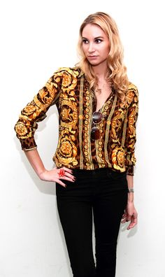 EW's Assistant Beauty Editor, Elizabeth embraces a little Seventies style with this silk Versace shirt, gold aviators and dark wash denim.