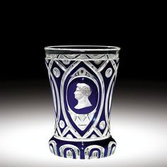 Overlay Beaker with Sulphide Bust - Circa 1841-1851 Bohemia - Very thick colorless glass, cased with opaque white, then sapphire-blue; free-blown with design cut through to colorless core or base. Long sides spreading in slight concave curve from projecting base to plain rim; geometric design, opaque white piping between colorless (core) reserve and blue surface ground -- on sides, wide band having discs in ends of vertical intersecting ellipses and, in front, large ellipse with portrait…