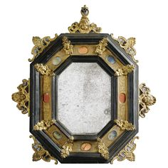 An Italian gilt-bronze, copper and hardstone-mounted ebonised frame, 17th C. now mounted as a mirror, apron mount missing 34cm. high, 31cm. wide; 1ft. 1½in., 1ft ¼in.