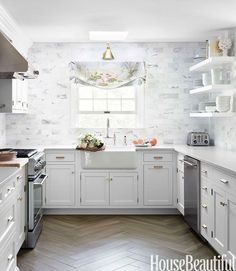 Kitchen Dreams. Swirling grays and gleaming brass warm up a classic white kitchen. Interior Designer: Caitlin Wilson.