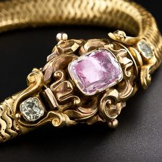 This rare and resplendent Georgian bracelet from the 1840's is a collector's dream. The centerpiece of the bracelet (which also conceals it's clasp) has simply masterful scrolling leaf and flower gold repousse work, and features a shimmering lavender-pink, foil-backed cushion topaz and two glittering cushion chrysoberyls. The body of the bracelet is slinky, sumptuous, and exquisitely wrought. Measures 7 1/2 inches lon