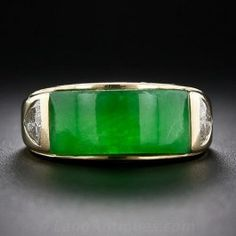 A thick and translucent vibrant green 'saddle' jade curves around the finger and is met at each end with a sparkling trillion diamond in this sleek and very cool estate gent's ring produced during the latter-twentieth century in Los Angeles by a notable manufacturer of predominantly gent's rings - George Barmache. .70 carat total diamond weight. The inside of the 18 karat gold ring shank is stamped: GB. The jade measures about 5/8 inch by 5/16 inch.