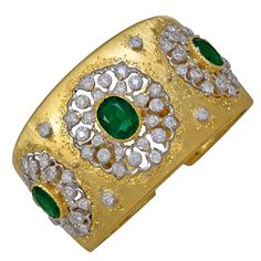 Spectacular 18K gold emerald and diamond cuff made and signed by M. Buccellati. Three gemset sections, each with a large faceted center emerald surrounded by brillant diamonds. The emeralds have a deep rich natural green color. The diamonds are white and sparkling. The distintive gold finish is in pristine condition. The cuff has an invisible hinge