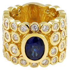 A bold and beautiful 18k gold ring featuring a 3 carat sapphire and approximately 5 carats of diamonds bezel set into thick walled gold tubes. The tubes are then assembled together to create a ring that is both stylish and rugged. Circa 1980s