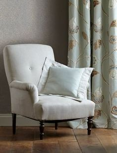 Draped floral fabric: Oriel Fabric on chair: Linenfold. Available in 4 colours, it provides a stylish backdrop for the decorative fabrics in the Oriel Silks collection.  A rub of 10,000 makes this suitable for light upholstery as well as curtains and cushions.