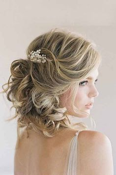 Wouldn't you like your wedding hairstyle to be like this timeless and elegant cut? Pairing a wreath with big barrel curls and soft, side swept bangs enhance any wedding haircut. This curly hairstyle for wedding is romantic enough and equally beautiful. An oval brooch adds classic vibe to the hairstyle.