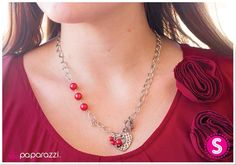 An adorable heart charm in an antiqued finish is hammered with texture and decorated with a smaller heart silhouette at its center. A cluster of red pearls and a red crystal bead accents the heart charm, while matching red pearls climb the side of a classic silver chain. Features a toggle clasp closure.  Sold as one individual necklace. Includes one pair of matching earrings.
