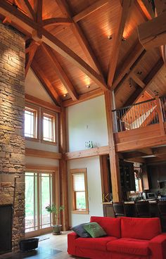 This timber frame great room in Kentucky has multiple king post trusses and intricate hand forged stair/balcony railings.