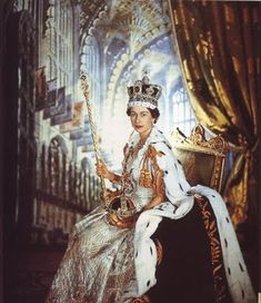 """Queen Elizabeth on her Coronation Day June 2, 1953. Her Majesty is wearing the purple Coronation Robe trimmed with ermine, gold Garter Collar and dress of white satin with coloured beaded embroidery of the flower emblems of Great Britain and the Dominions, among them the English Tudor rose, Scottish thistle, Irish shamrock, Welsh leek, Canadian maple leaf, Australian wattle and Indian lotus flower."""
