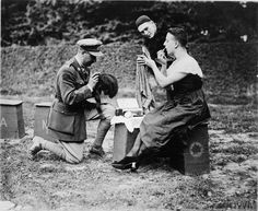 """Leisure and entertainment at the Front: A female impersonator of the """"Maple Leaves"""", the Canadian Concert Party, making up for his role in a field on the Western Front. With women rarely permitted close to the front line, most concert parties had an actor who specialised in female roles."""