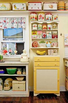 This lovely 1950's-style vintage kitchen is a treasure to see. Bright splashes of primary colors coming from the cookie jars and storage spaces make the kitchen dreamy.