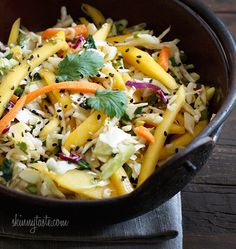 Asian Cabbage Mango Slaw recipe - Light, fresh and crisp slaw made with shredded cabbage, carrots, lime juice, rice vinegar and a slightly under-ripe mango topped with sesame seeds. A perfect side to fish, pork and even burgers.