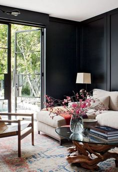 Black + white family room with foliage, branches, + stacked books.