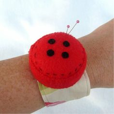 red button wrist pincushion made of felt and a large, flat bottlecap to keep pins from stabbing through to the arm