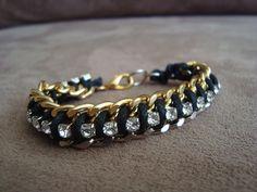 Pulseira trançada com duas correntes em metal nas cores prata e dourado, fio de cera preto e strass branco.  Comprimento: 17cm R$49,90
