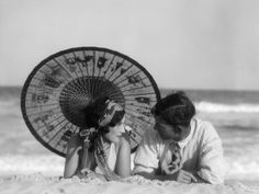 1920s Romantic Couple Looking At One Another Laying Face To Face Under Parasol On Sandy Beach Photographic Print