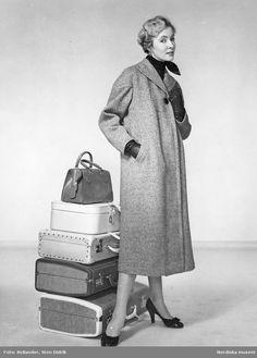 Modell i kappa, scarf, handskar och pumps. Handväska ovanpå resväskor. Fotograf: Sten Didrik Bellander, ca 1953-1957