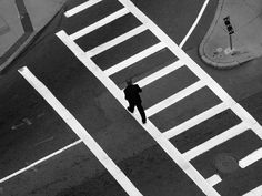 A man crosses the street in downtown Boston on November 11, 2015.