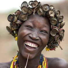Creative: A young woman laughs as she shows off her elaborate hairstyle made from a mixtur...
