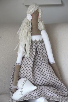 La he vestido con una tela de lino color piedra y unos topitos morados