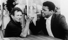Ali arm-wrestles with novelist Norman Mailer, who would later write a critically acclaimed book on Ali called The Fight.