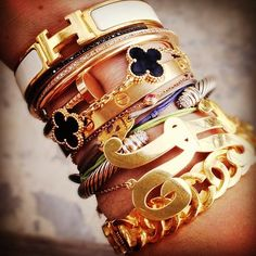 Hermes, Van Cleff & Arpels, Chanel, and assorted bracelets stacked...