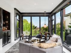 Painting window trim black allows the windows to pop and frame the outside view. The family room designed by Steven Miller Design Studio offers a scenic view of the surrounding San Francisco hills that rivals many landscape pantings and photography.