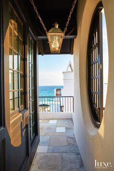 A passageway leads to the terrace overlooking the ocean. An oval shutter was custom-designed for the window opening formed in the parapet; opposite the oval window is a small room for relaxing. The lantern by Bevolo Gas and Electric Lights is secured with stainless-steel chain on four sides to protect it from wind.