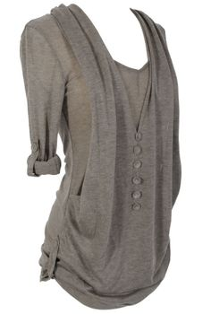 This knit tunic is stylish, yet comfortable—it is perfect to wear on lazy days at home or when you're out running errands. You'll want one in every color! It features a simple knit V neck top with rolled up half sleeves. The second layer is a faux drape vest with a vertical row of buttons at the front. This little top looks great paired with denim and flats for a casual day look. great with comfy yoga's as an alternative to sweats  around the house. Available in Ivory, Coral, & Black.