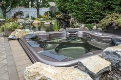 """Natural Looking Backyard Retreat: This project included a natural looking waterfall feature with the pond, moss rock boulders and lush landscaping around the pond and spa.  The clients' """"in-tub views"""" are spectacular; they also enjoy wonderful hydrotherapy options due to Bullfrog Spa's individual, inter-changeable massage JetPaks, which our clients say, always hit the spot.  http://longislandhottub.com/custom-installations.php"""