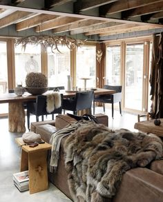 Woodsy rustic urban, leather sofa, faux fur throw, lots of windows