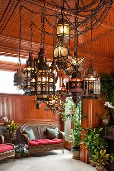 An exotic chandelier made up of antique Moroccan lanterns hangs from the ornamental beadboard ceiling in the conservatory.