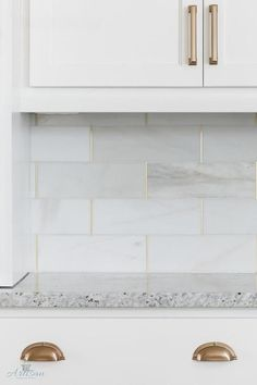 A unique backsplash displays Honed White Tiles with Gold Trim.