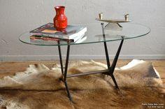 """<p style=""""text-align: justify;"""">Dessinée par Angelo Ostuni, cette table basse des années 50 est pleine d'audace et de modernité. Les lignes franches, presque tranchantes du piétement lui donnent un côté graphique et géométrique. Cette table basse vintage tire son dynamisme enthousiasmant de ses lignes remarquables... Reflet de la création d'une époque, elle porte encore aujourd'hui un modernisme époustouflant. Ultra design, elle apportera pep's et originalité à votre salon.</p>"""