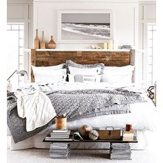 Large king size bed with grey and white sheets and a wooden headboard