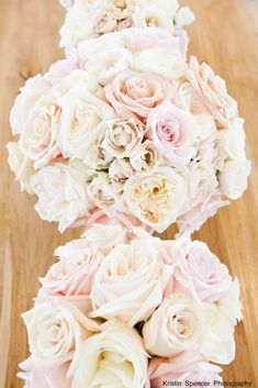 Bridesmaids will carry cream hydrangeas, ivory garden roses, and blush spray roses wrapped in navy and white striped ribbon