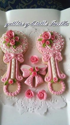 Sugar Cookies With Royal Icing Decorations of Pink Baby Rattle and Baby Bow.